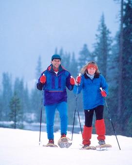 Schneeschuhwandern im wald auf dem berg kapuze