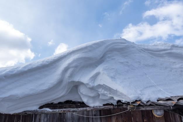 Schneewehe auf dem dach gegen den blauen himmel mit wolken, nahaufnahme. schneewehe nach einem schneesturm. wellenförmige oberfläche einer schneewehe. abstraktes wirbelndes schneegestaltungselement, plan, hintergrund