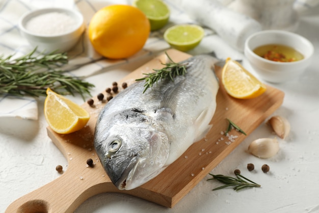 Schneidebrett mit dorado-fisch und kochzutaten auf weiß