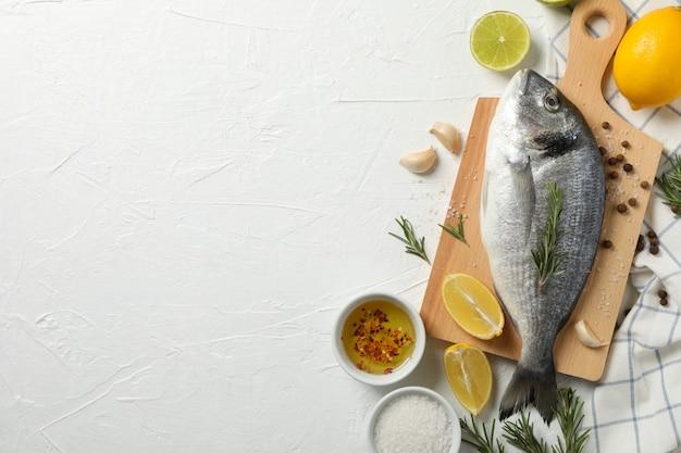 Schneidebrett mit dorado-fisch und kochzutaten auf weißem hintergrund, platz für text