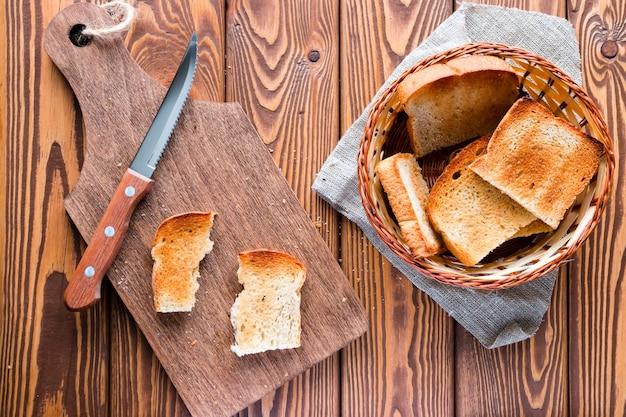 Schneidebrett mit einem messer und einem korb des toasts auf einem hölzernen