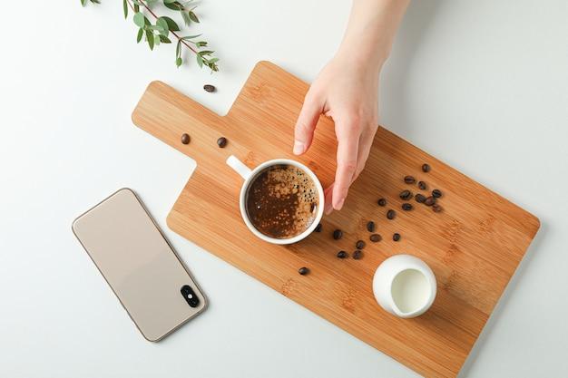 Schneidebrett mit tasse frischem kaffee, milchkaffeebohnen, telefon, weiblichen händen