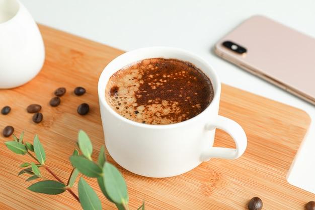 Schneidebrett mit tasse frischem kaffee, telefon und pflanzenzweig auf weißem hintergrund