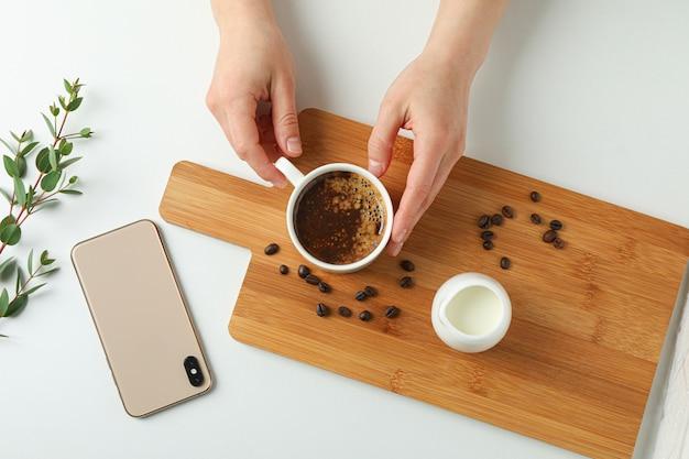Schneidebrett mit tasse kaffee, kaffeebohnen, telefon und pflanzenzweig auf weißem hintergrund