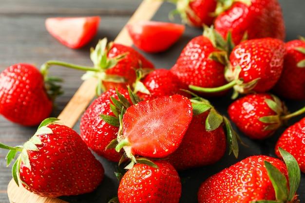 Schneidebrett und frische erdbeeren auf holztisch, nahaufnahme und platz für text. sommer süße früchte und beeren