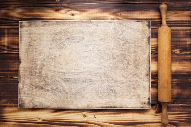 Schneidebrett und nudelholz auf rustikalem holzbretthintergrund, draufsicht