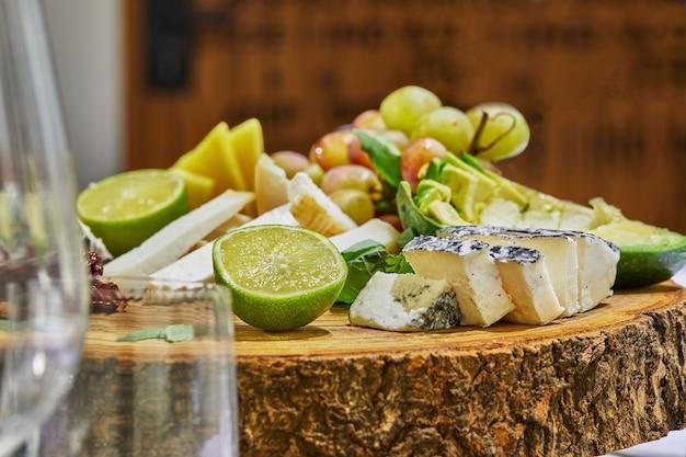 Schneiden ausgewählter käsesorten auf einem holzbrett mit trauben, limette, ananas und kräutern