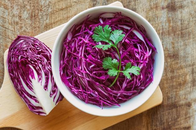 Schneiden oder schneiden sie frischen purpur- oder rotkohl in der weißen schüssel und verzieren sie mit koriander
