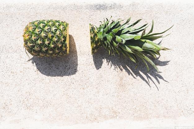 Schneiden sie ananas auf dem swimmingpool.