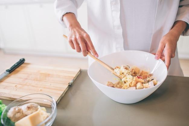 Schneiden sie ansicht der hände des mädchens, die salat in der weißen schüssel mischen. dafür benutzt sie einen löffel. mädchen trägt weißes hemd. sie kocht.