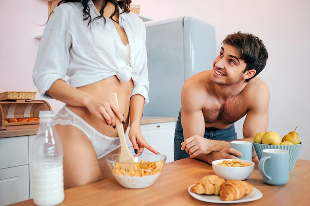 Schneiden sie ansicht des sexy standes der jungen frau in der küche bei tisch. sie mischt cornflakes mit milch in einer schüssel. aufgeregter junger mann schaut sie an und lächelt. er hält eine tasse.