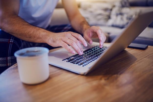Schneiden sie bild des kaukasischen mannes im pyjama aus, der im wohnzimmer sitzt und auf tastatur tippt. auf dem tisch stehen laptop und tasse mit kaffee. morgens.