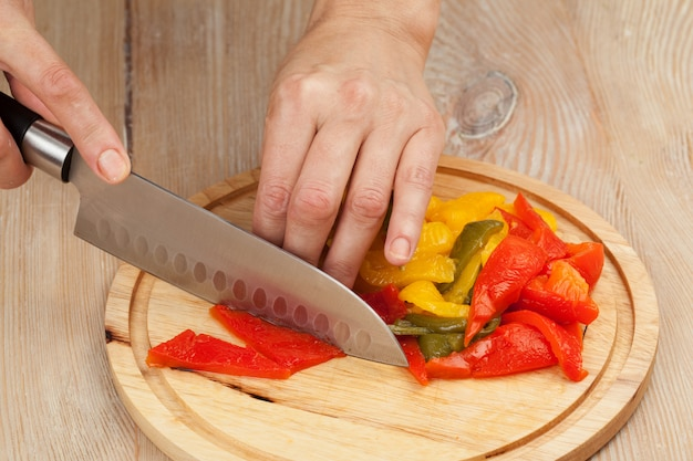Schneiden sie das gemüse mit einem küchenmesser auf dem brett