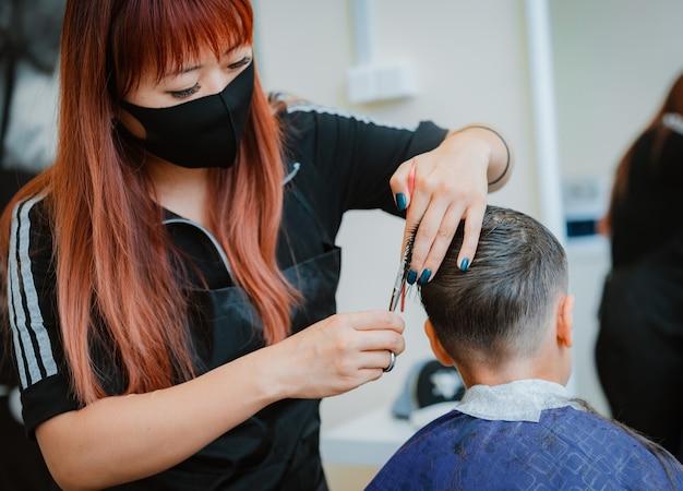 Schneiden sie das kind dem kunden mit sicherheitsmaßnahmen ab. asiatischer friseur. wiederaufnahme der arbeit mit barbershop-sicherheitsmaßnahmen im kontext der covid-19-pandemie