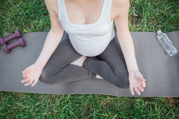 Schneiden sie die ansicht der jungen schwangeren frau, die in der lotoshaltung im park allein sitzt. sie meditiert über yoga mate. violette hanteln und daneben liegende wasserflasche.