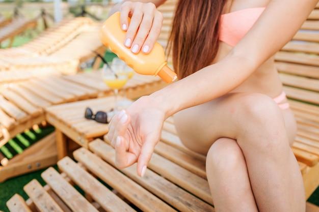 Schneiden sie die ansicht des mädchens sitzend auf sunbed. sie hat die beine gekreuzt und etwas sonnenschutzcreme zur hand gegeben. mädchen hält orange flasche in der rechten hand.