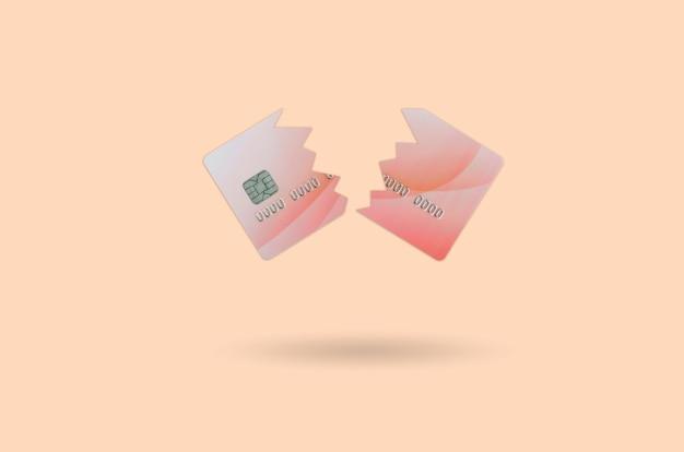 Schneiden sie die gebrochene rote kreditkarte, die auf orange lokalisiert wird