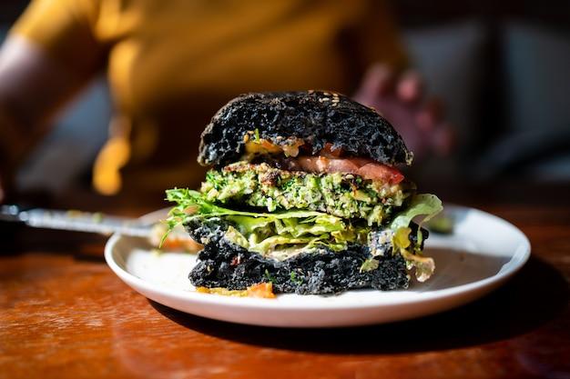 Schneiden sie die hälfte des brokkoli-quinoa-holzkohle-burgers mit guacamole, mango-salsa und frischem salat auf einem weißen teller. kreatives veganes essen für vegetarier.