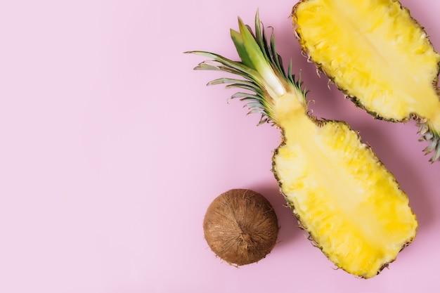 Schneiden sie die hälften der frischen ananasfrucht mit der ganzen kokosnuss auf pastellrosa hintergrund