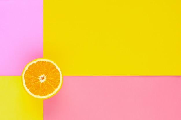Schneiden sie die orange frucht, die auf buntem hintergrund für sommerzeit lokalisiert wird.