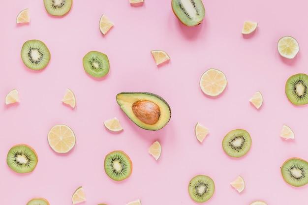 Schneiden sie die zitrusfrucht und kiwi, die um avocado liegen