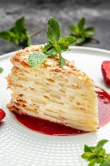 Schneiden sie einen kuchen aus blätterteig mit sahne, äpfeln und erdbeermarmelade, dekoriert mit minze. zarter und luftiger kuchen. vertikales bild. ansicht von oben