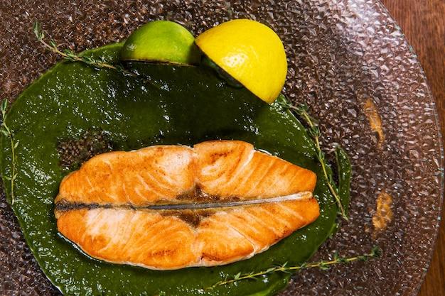 Schneiden sie fische mit zitrone und soße in glasplatte auf holztisch im luxusrestaurant