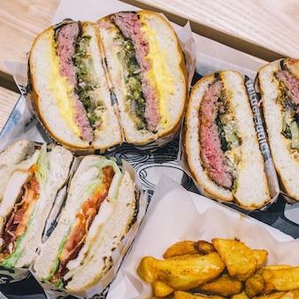 Schneiden sie fleischburger und pommes frites auf einem tablett in einem cafe