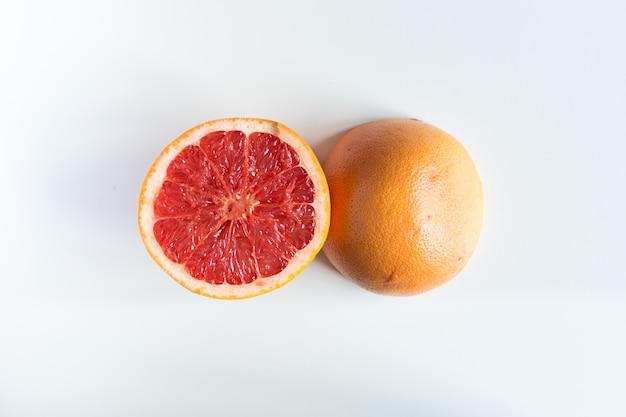 Schneiden sie frisch grapefruit zur hälfte auf einem weißen hintergrund