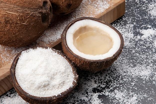 Schneiden sie frische kokosnuss mit echter kokosmilch auf einem dunklen tisch mit kokosflocken. vitaminfrüchte. gesundes essen