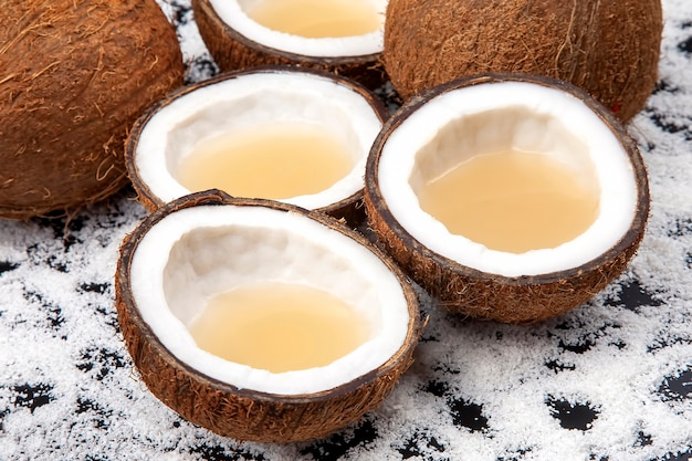 Schneiden sie frische kokosnuss mit echter kokosmilch auf einem dunklen tisch mit kokosflocken.