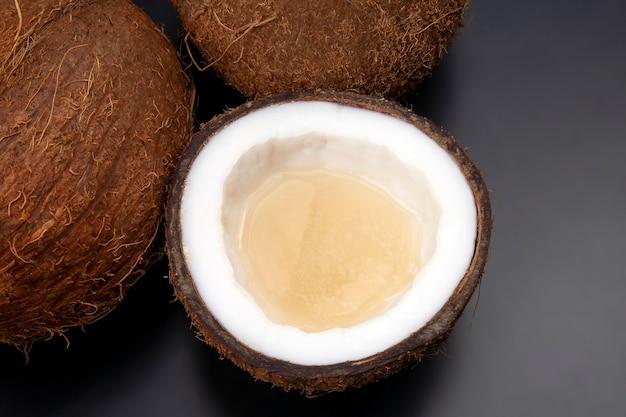 Schneiden sie frische kokosnuss mit echter kokosmilch auf einem dunklen tisch.