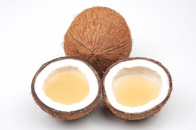 Schneiden sie frische kokosnuss mit echter kokosmilch auf einem weißen hintergrund. vitaminfrüchte. gesundes essen