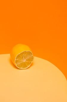 Schneiden sie frische zitrone auf eine gelb-orange