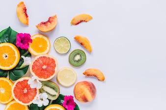 Schneiden Sie Früchte in der Nähe von Blättern und Blüten