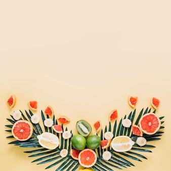 Schneiden sie früchte und palmblättern zusammensetzung