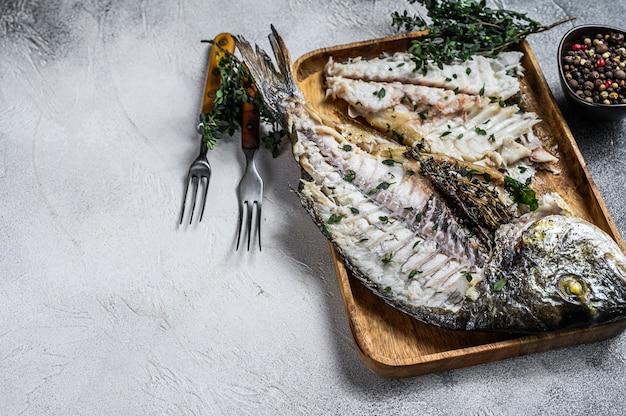 Schneiden sie gebackenen seebrassen-dorado-fisch in ein holztablett.