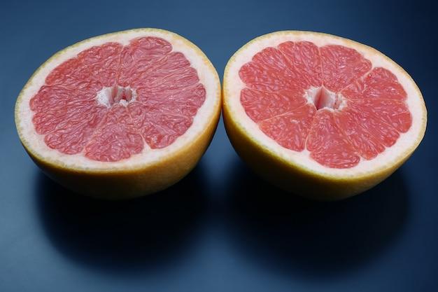 Schneiden sie grapefruit auf einem dunklen hintergrund