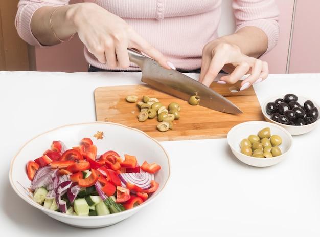Schneiden sie grüne oliven auf einem schneidebrett, um sie einem salat hinzuzufügen.