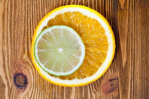 Schneiden sie nebeneinander liegende orangen- und limettenscheiben und fotografieren sie sie in nahaufnahme. kleine schärfentiefe