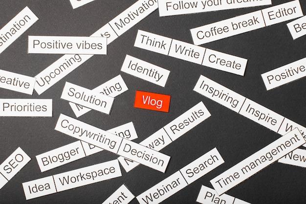 Schneiden sie papieraufschrift vlog auf einem roten hintergrund, umgeben durch andere aufschriften auf einem dunklen hintergrund. word-cloud-konzept.