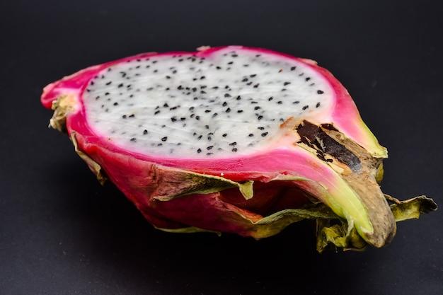 Schneiden sie pitahaya auf schwarzem hintergrund nahaufnahme, schneiden sie drachenfrucht