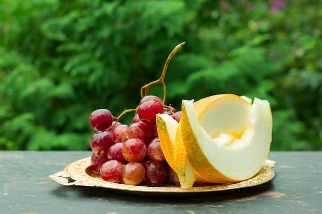 Schneiden sie scheiben der reifen gelben melone und der weintraube auf einer tabelle mit natürlichem grünem hintergrund.