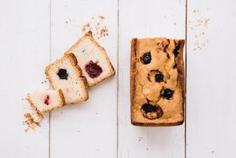 Schneiden Sie Torte mit Stau auf Holztisch