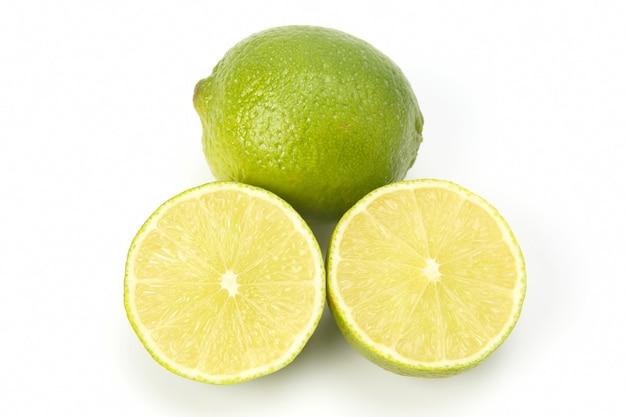 Schneiden sie zitrusfrüchte der grünen zitrone auf weiß