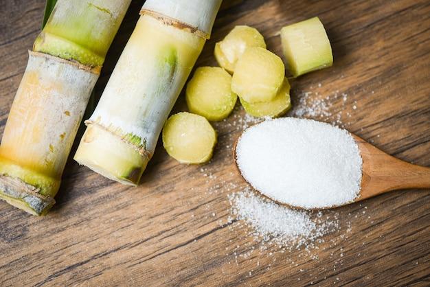 Schneiden sie zuckerrohrstück und raffinierten zucker auf hölzernem löffel