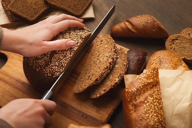 Schneiden von brot auf holzbrett. unerkennbare köchin, die gesunde sandwiches zubereitet, draufsicht, kopierraum