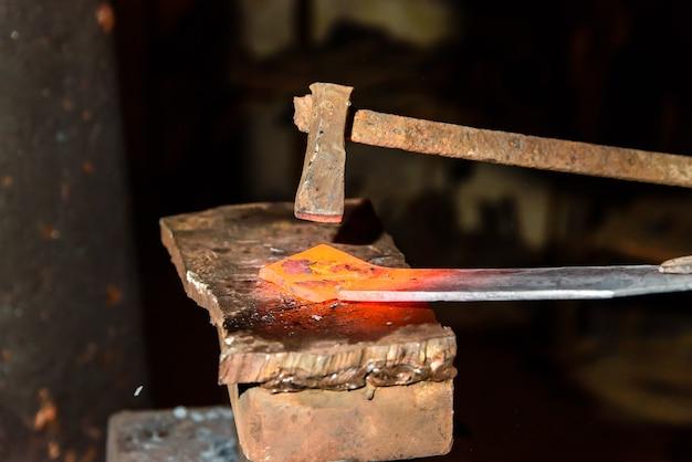 Schneiden von heißem metall in der schmiede.