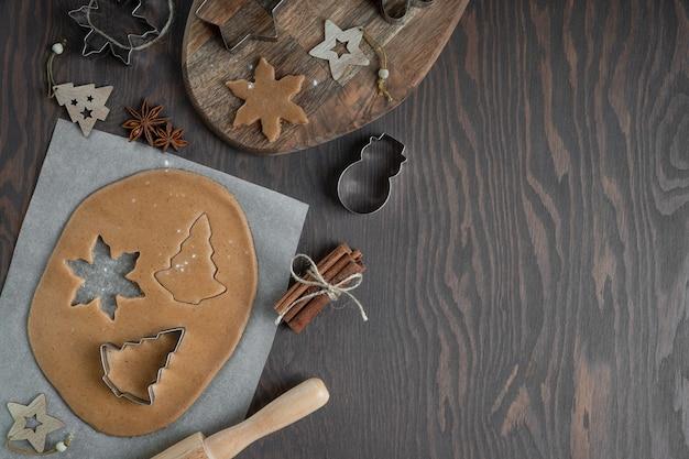 Schneiden von lebkuchen aus herzhaftem teig mit schneidern auf dunklem holztisch mit anis