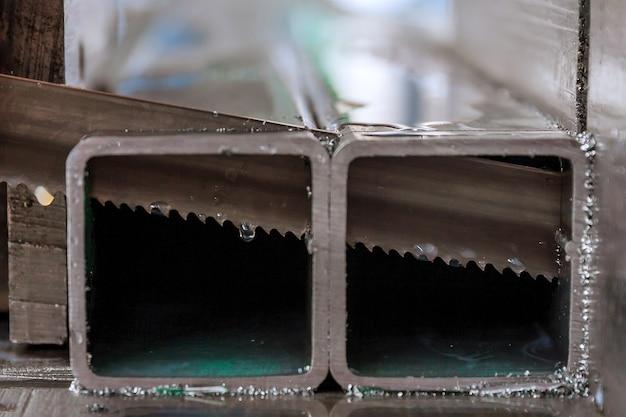 Schneiden von stahlprofilen und rohren auf einer bandsäge in der produktion.